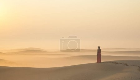 woman standing on sand dune