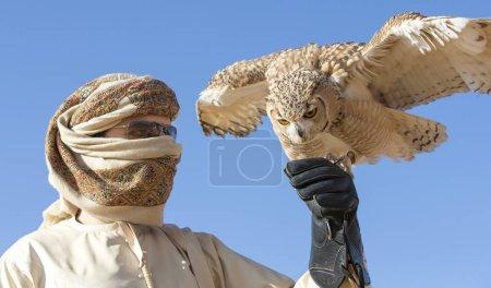 Photo pour Falconer en tenue traditionnelle formation désert hibou dans un désert près de Dubai - image libre de droit
