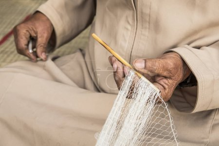 Hands working on making fish net