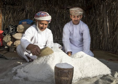 Photo for Muscat, Oman, February 4, 2017: omani men in traditional clothing with a pile of salt, shifting - Royalty Free Image