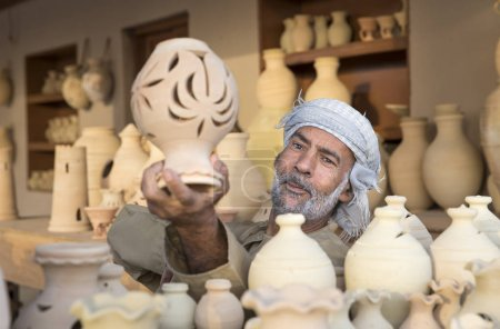Photo for MUSCAT, OMAN - FEBRUARY 4TH, 2017: omani craftsman selling clay jars - Royalty Free Image