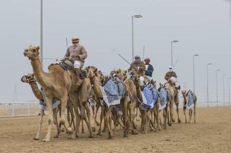 men riding camels in desert