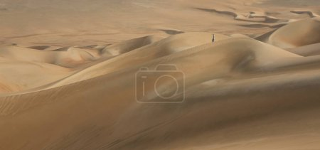 man walking in sand dunes
