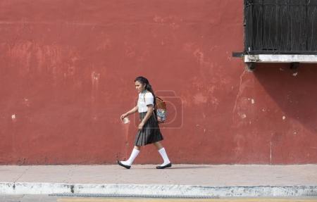 schoolgirl in school uniform walking on street