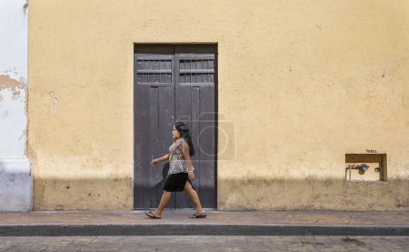 woman walking in front of old house
