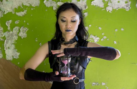 Photo pour Jeune femme à l'intérieur d'une maison abandonnée avec une horloge d'heure courant dans le temps - image libre de droit