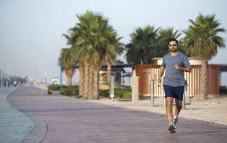 man running on a running track near beach