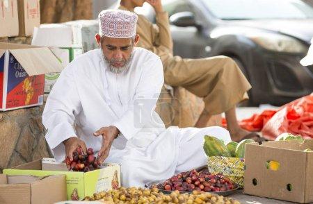 man selling dates at street market