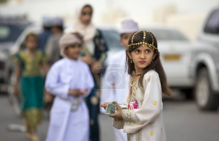 girl  in traditional Omani outfit at toy market