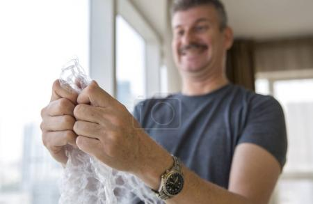 man popping bubble wrap