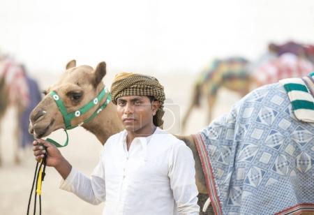 Photo pour Rub al Khali Desert, Abu Dhabi, Émirats arabes unis, 22 juillet 2017 : homme avec son chameau sur une piste de chameaux dans un désert - image libre de droit