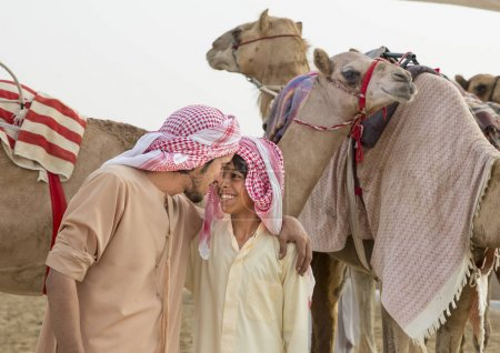 man and boy training camels