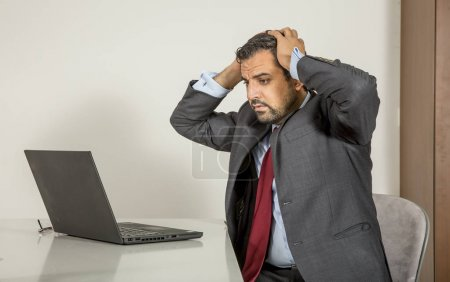 Photo for Middle aged arab businessman in grey suit working at home using laptop - Royalty Free Image