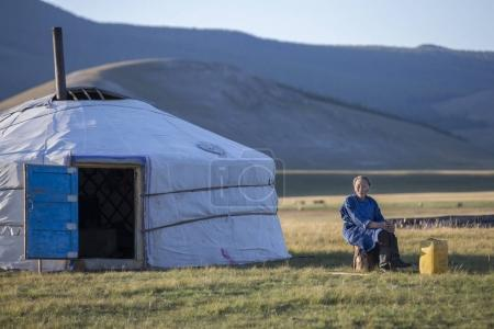 mongolian woman resting outside her ger