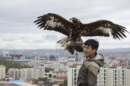man with eagle on rooftop