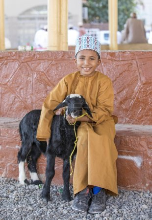 Nizwa, Oman, 10th November 2017: omani kid with goatling at goat market