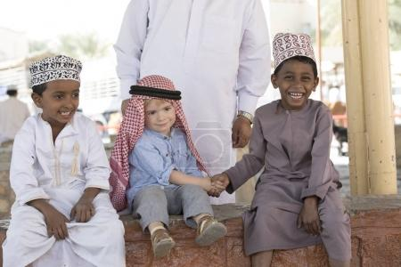 Nizwa, Oman, 10th November 2017: omani kid and european kid shaking hands while sitting on parapet