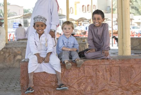 Nizwa, Oman, 10th November 2017: omani children and european kid sitting on parapet