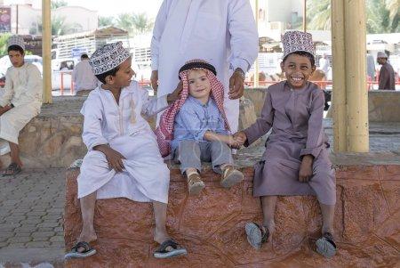 Nizwa, Oman, 10th November 2017: omani kid with caucasian kid shaking hands and smiling