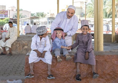 Nizwa, Oman, 10th November 2017: old omani man talking to kids at goat market