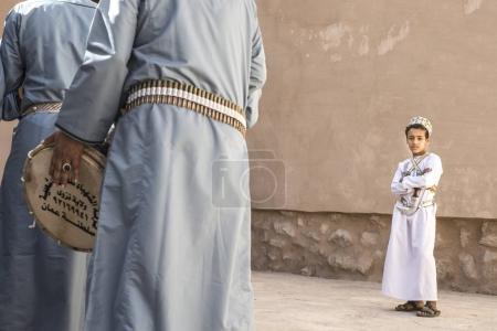 Nizwa, Oman, December 1st, 2017: omani boy looking at men celebrating a national day