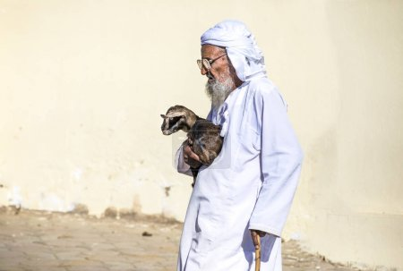 Sinaw, Oman, November 30th, 2017: old man carrying a baby goat at Sinaw market