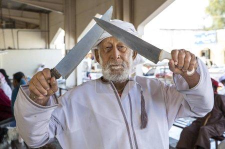 Sinaw, Oman, November 30th, 2017: old man showing off his knives