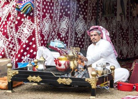 Abu Dhabi, United Arab Emirates, December 8th, 2017: arab man making coffee and sitting at decorated table