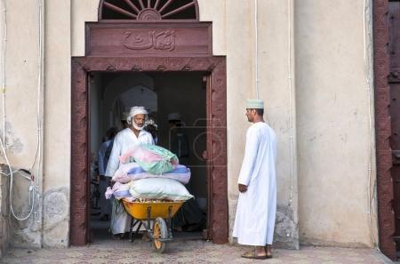 Nizwa, Oman, December 1st, 2017: the arabian man takes out the goods for sale on a wheelbarrow