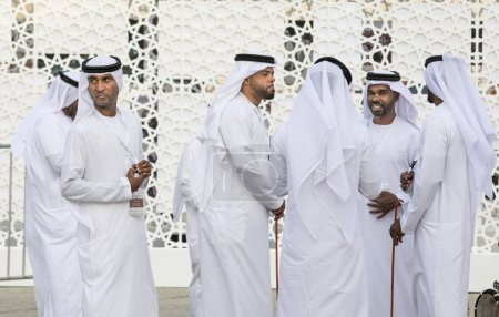 Abu Dhabi, United Arab Emirates, December 8th, 2017: emirati men in traditional clothing conducting a conversation