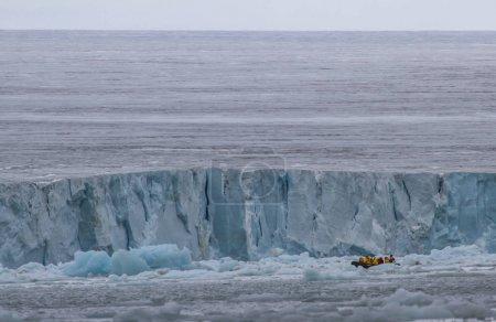 Photo pour Personnes voyageant en zodiaque entre icebergs de Svalbard - image libre de droit