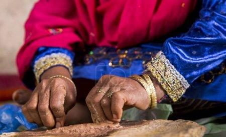 hands of an Omai woman grinding sandalwood