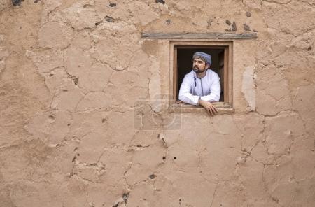 Photo pour Homme arabe en tenue omani traditionnelle dans un vieux château - image libre de droit