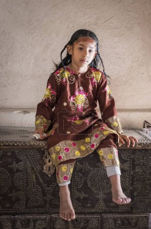 NIZWA, OMAN - 24TH MARCH 2018: Omani girl in traditional clothing sitting on an old chest