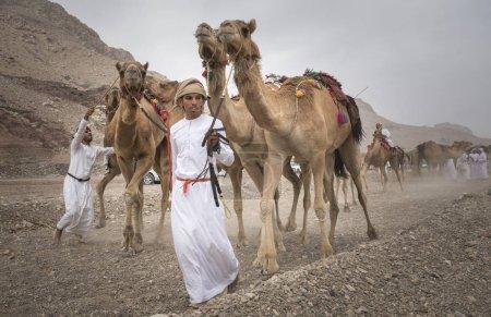 Photo pour Khadal, Oman - 7 avril 2018 : hommes omani avec chameaux sur une route de campagne poussiéreuse - image libre de droit