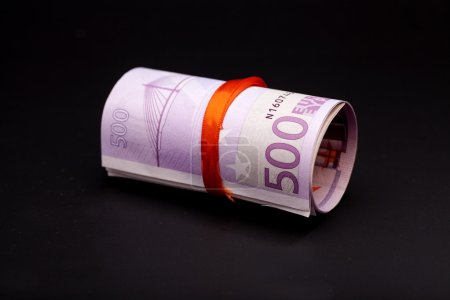 500 euro money in  red ribbon on black