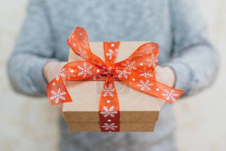 Man holds a Christmas gift in her hands