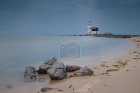 Misty sea and lighthouse on rocky coast