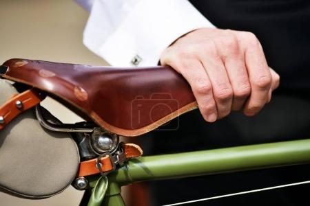 Man's hand on bicycle saddle