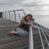 Trauriges Mädchen sitzen auf der alten Liegeplatz