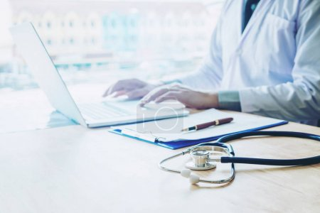 Doctor typing information on Laptop in Hospital office focus on