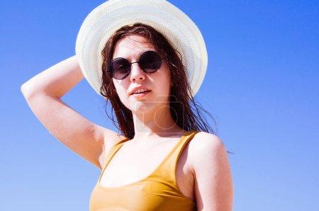 Photo pour Belle fille en lunettes de soleil et chapeau contre la mer - image libre de droit