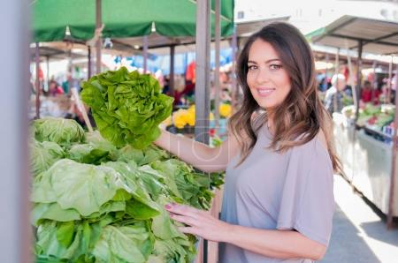 Portrait of beautiful young woman choosing green leafy vegetable