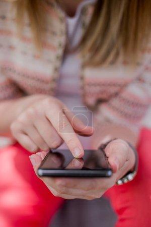 Photo pour Jeune femme utilisant mobile smartphone internet recherche ou téléchargement avec fond flou, style vintage, gros plan. Main des femmes utilisant un téléphone intelligent mobile - image libre de droit