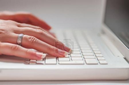 Fingers of woman pressing laptop keys