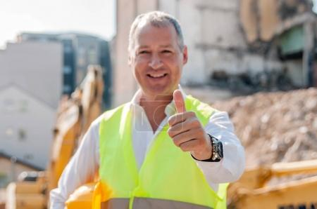 portrait of smiling civil engineer holding hardhat and showing thumb up gesture on construction site