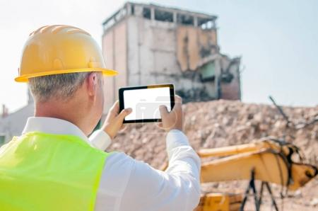portrait of civil engineer in yellow hardhat using digital tablet at construction site, back view