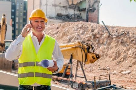Photo for Engineer talking on the phone on a construction site. Portrait of an handsome mature engineer. Confident architect holding rolled up blueprints at construction site - Royalty Free Image