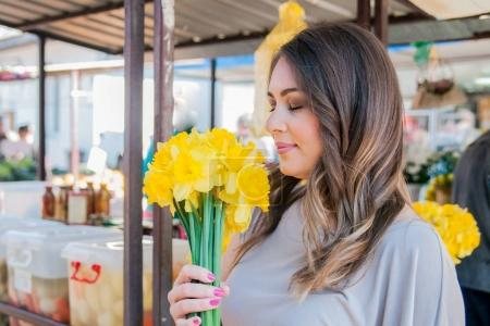 woman enjoying flowers in floral market