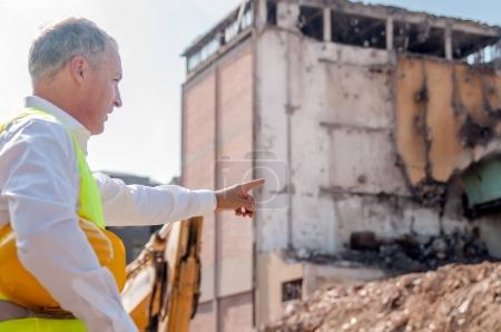 portrait of professional civil engineer holding hardhat inspecting construction site and pointing finger at building